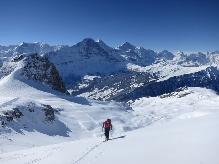 High Angle View Of Person Skiing On Snowcapped Mountain Against Clear Sky