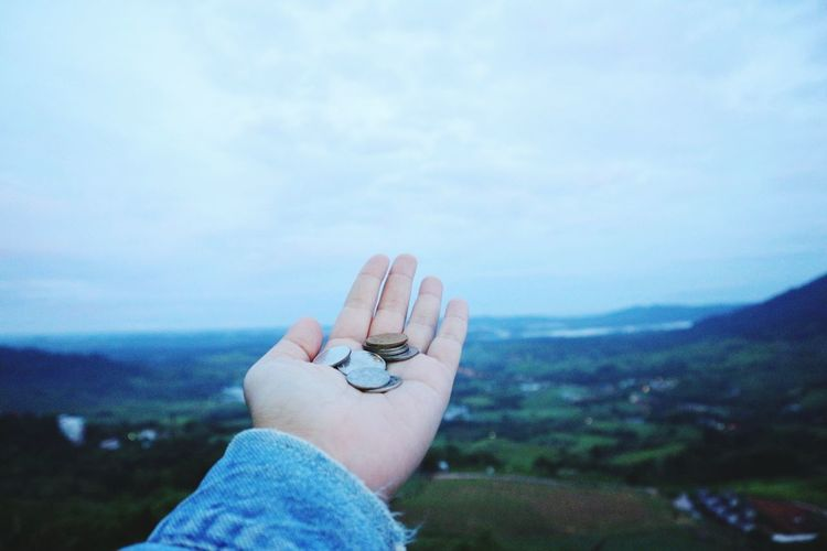 Cropped hand of woman holding coins against sky