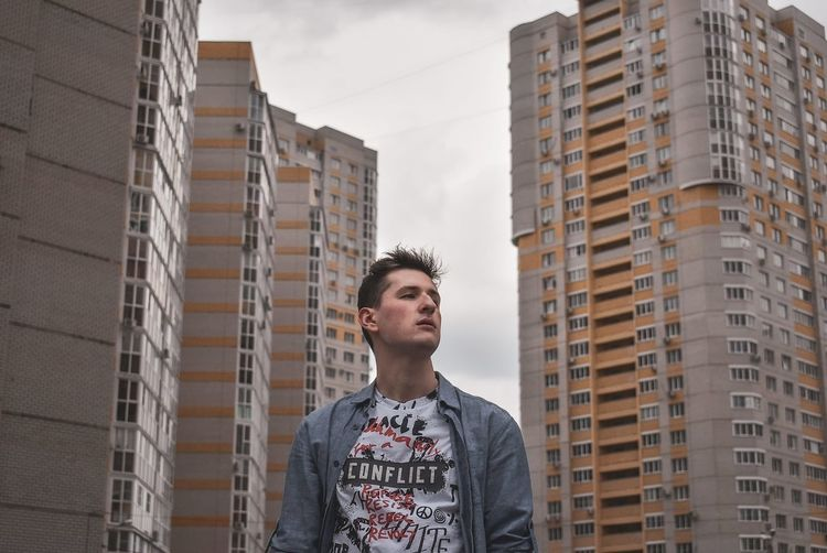 Low angle view of young man looking away against buildings in city
