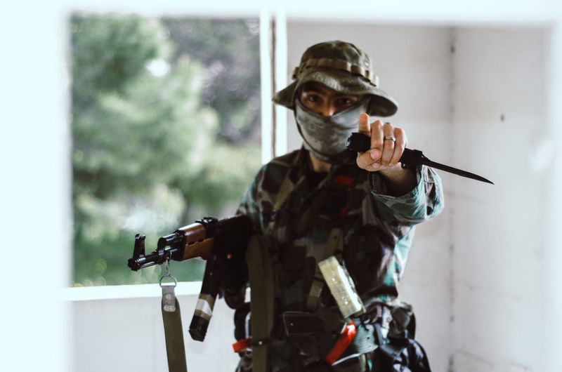 Special forces soldier holding rifle gun point finger at you looking at camera One Person Indoors  Weapon Front View Portrait Waist Up Gun Real People Holding Men Sport Mask Young Adult Focus On Foreground Young Men Protection Headshot Window Standing Obscured Face Government