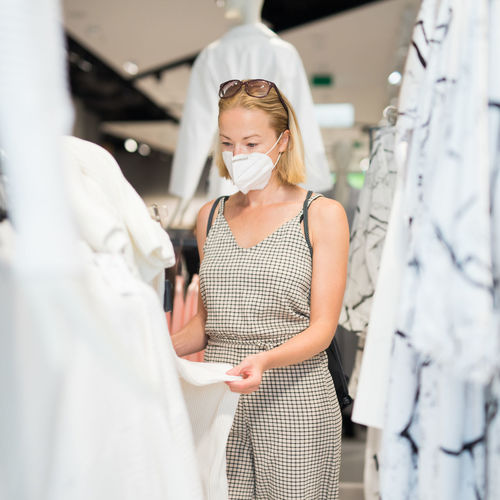Mid adult woman wearing flu mask shopping at clothing store