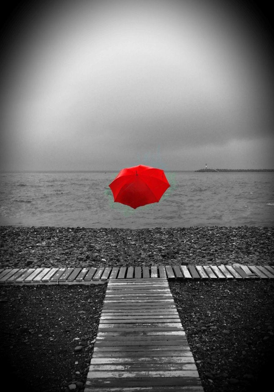 RED UMBRELLA AGAINST SEA DURING RAINY SEASON