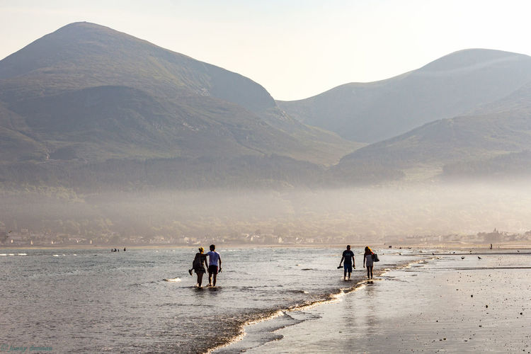 People walking at beach against mountains during sunny day