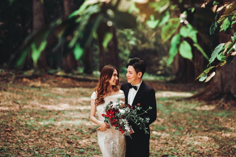 Young couple standing against plants