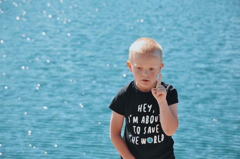 Full length of boy standing in sea