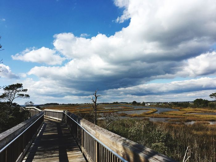 Footbridge over landscape against sky