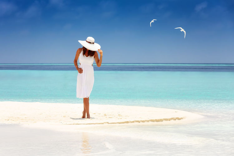 Attractive woman in white summer dress and sunhat stands on a beach surrounded by tropical, turquoise waters Sea Beach Water One Person Land Leisure Activity Horizon Over Water Lifestyles Standing Scenics - Nature Hat Turquoise Colored Sun Hat Outdoors Maldives Woman Dress White Vacations Holiday Tropical Climate Tropics Caribbean Travel Concept