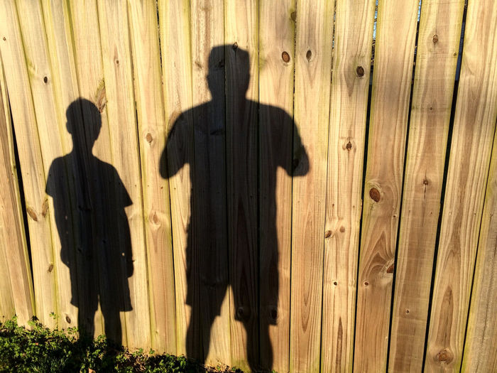 our lives are moving shadows that we wonder at until the sun sets. Black Boy Brown Day Ephemeral Fence Fencing Focus On Shadow Human Representation Moment Pattern Plank Shadows Silhouette Standing Sunlight Tan Textured  Wall - Building Feature Wood Wood Wood - Material Wooden