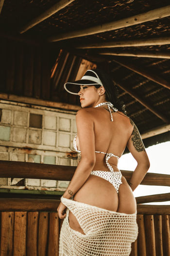 Rear view of woman in bikini standing n cottage