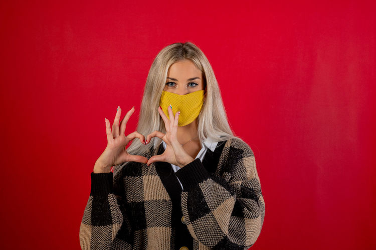 Portrait of young woman wearing mask making heart shape against red background