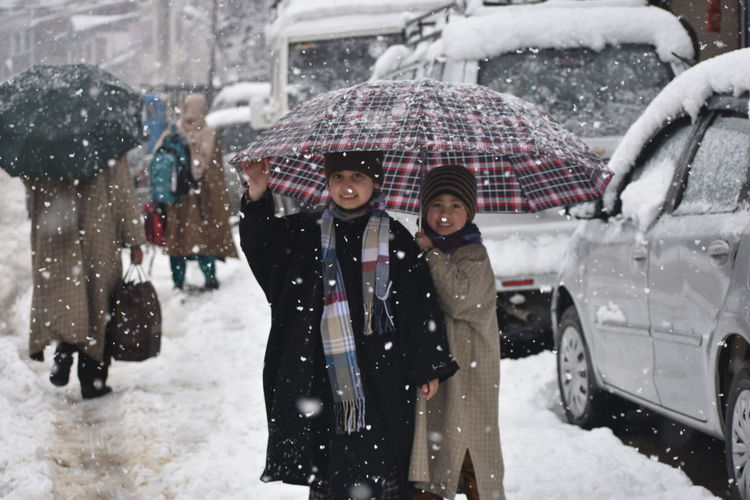 Couple of children take refuge under an umbrella during snowfall in Srinagar on Thursday. Warm Clothing Snowing City Snow Winter Cold Temperature Men Under Women Water Rainfall