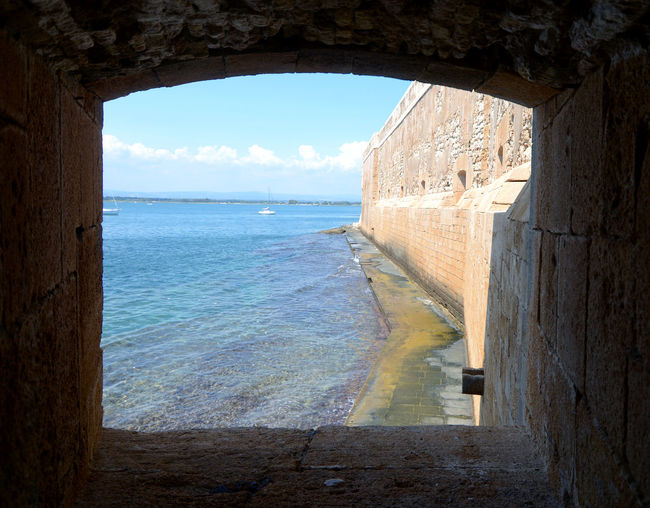 Syracuse / Italy – August 30, 2018: the Maniace castle is one of the most important monuments of the Swabian period in Syracuse and one of the most famous fortresses built by Frederick II of Swabia. Maniace Maniace - Ortigia Maniace Castle Mediterranean Sea Sicily Arch Arched Architecture Beach Beauty In Nature Built Structure Cloud - Sky Day History Horizon Horizon Over Water Indoors  Italy Nature No People Scenics - Nature Sea Sky Water Window