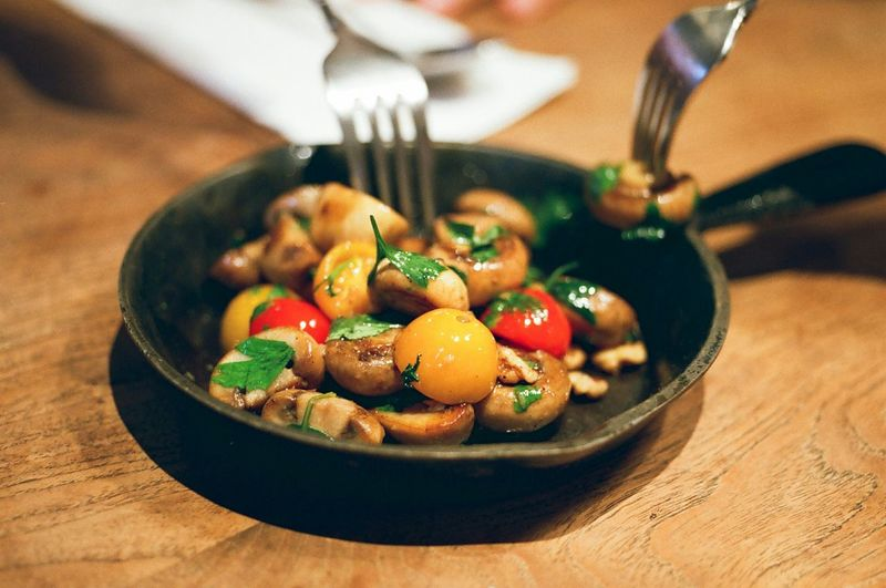 High Angle View Of Cooked Mushrooms With Cherry Tomatoes In Pan On Table