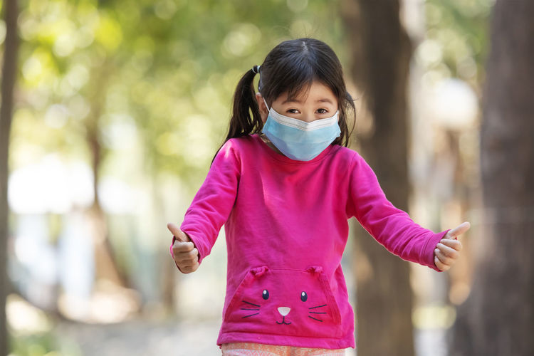 Portrait of girl wearing mask standing at park