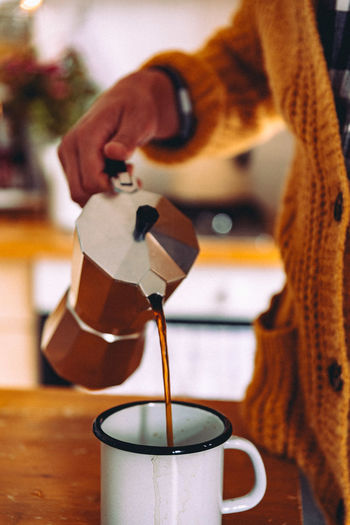 Midsection Of Woman Pouring Black Coffee In Mug