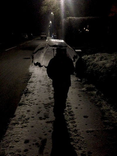 Dark whinter evening, out catching dragons in the snow FootPrint Street Light Child Night One Person Outdoors Rear View Shiluette Snow Street The Way Forward Umbrella