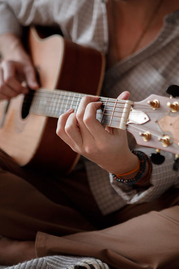 Midsection of man playing guitar