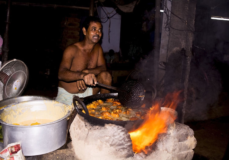 Shirtless man preparing food