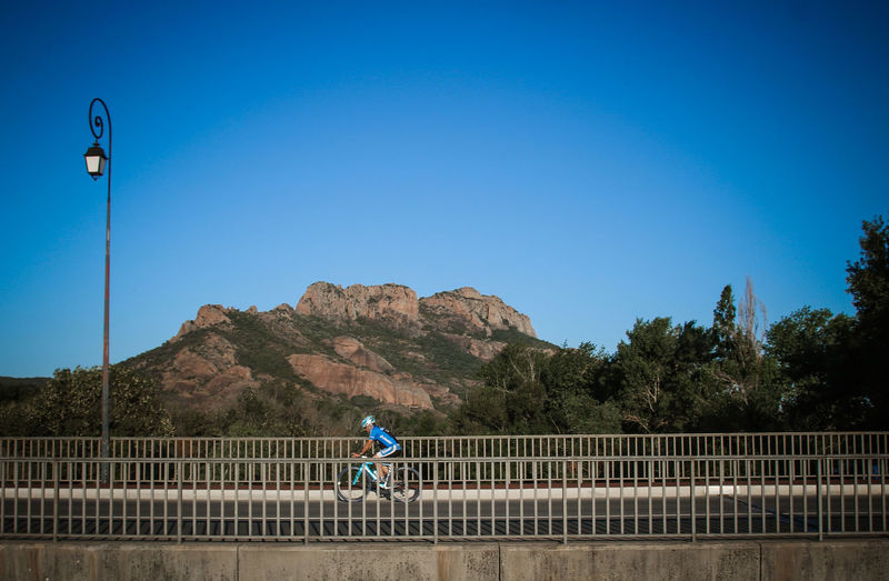 Man riding bicycle on road against clear blue sky
