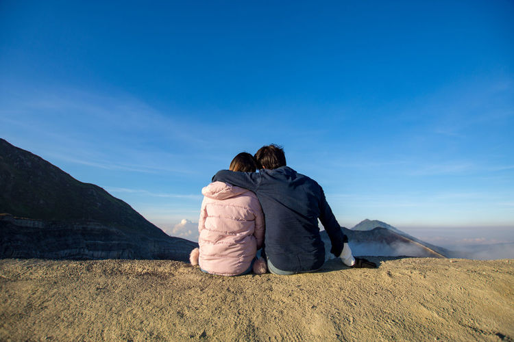 Rear view of couple sitting on land against sky
