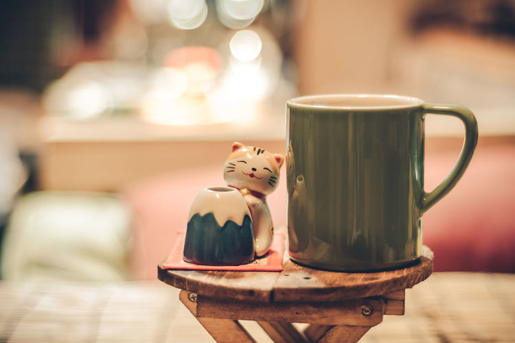 Close-up of cat toy and coffee cup on table at cafe