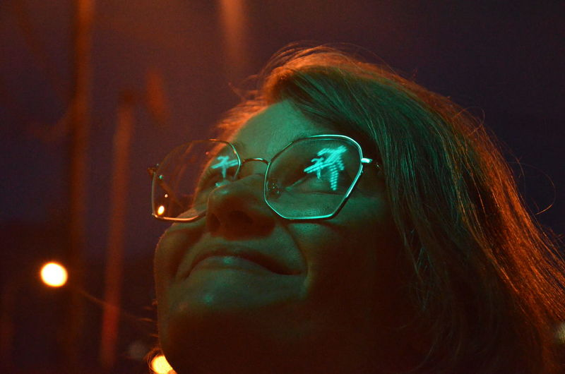 Close-up of smiling woman wearing eyeglasses looking up at night