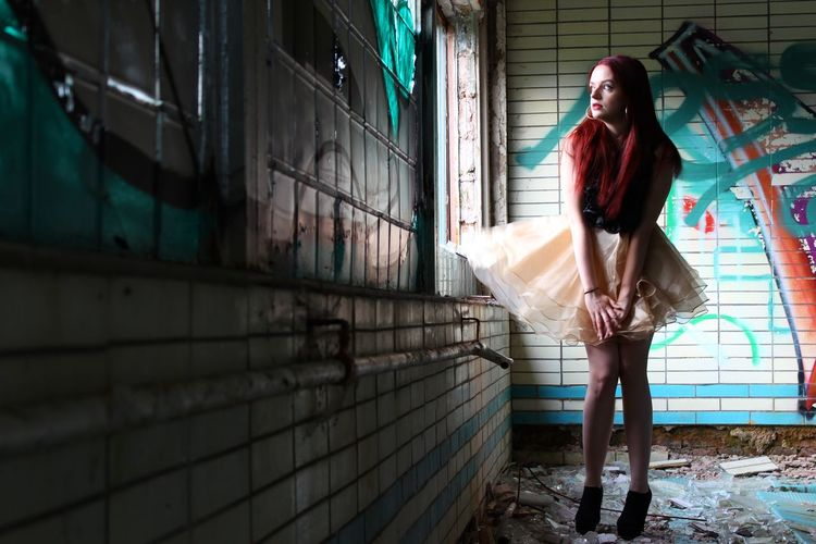 Full length of beautiful woman standing in abandoned building
