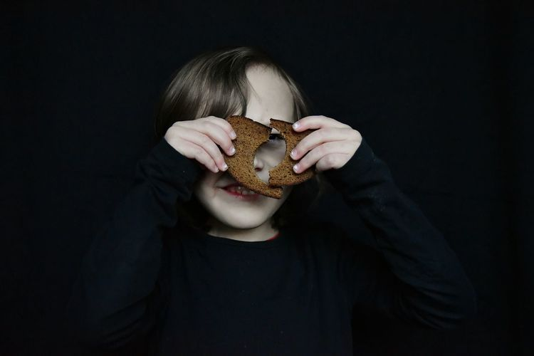 Bread Slice Of Bread Hole Broken Looking Smiling Elementary Age Kid Boy Fun Black Background One Person People Studio Shot Indoors  Human Body Part Healthy Eating Human Hand
