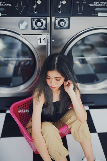 High angle view of woman sitting in basket by washing machine