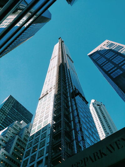 Low angle view of 432 park avenue against blue sky