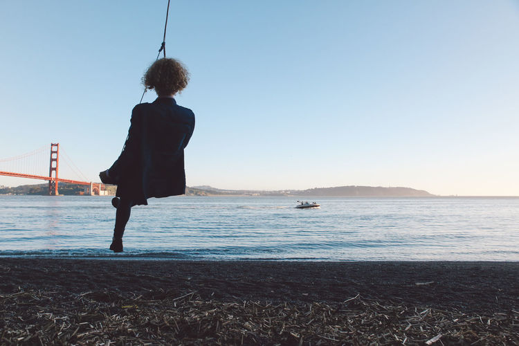 Rear view of young woman swinging at beach against clear sky