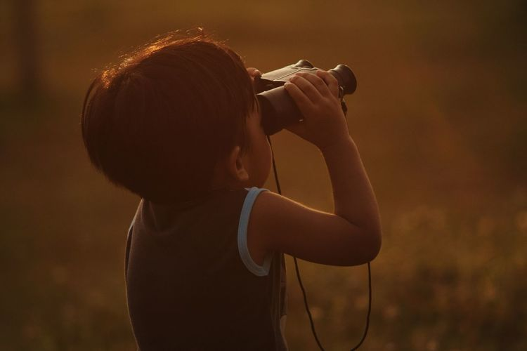Boy with binocular in beautiful golden moment Focus Touching Moment Golden Hour Creative Idea Sign Symbol Perspective Conceptual Concepts Boys Kids Icon Advertisement Business Commercial Connection Nature Wallpaper Website EyeEm Best Shots Expression Water Men Standing Rear View Young Women Close-up Camera EyeEmNewHere My Best Travel Photo