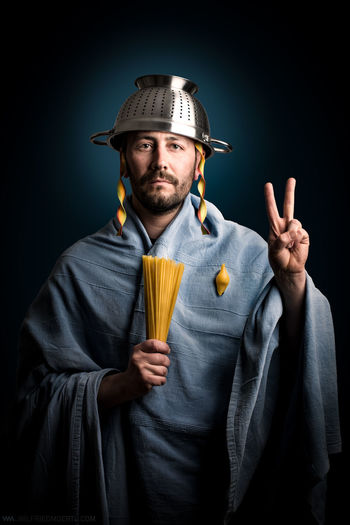Portrait of man holding uncooked pasta while wearing colander on head against black background