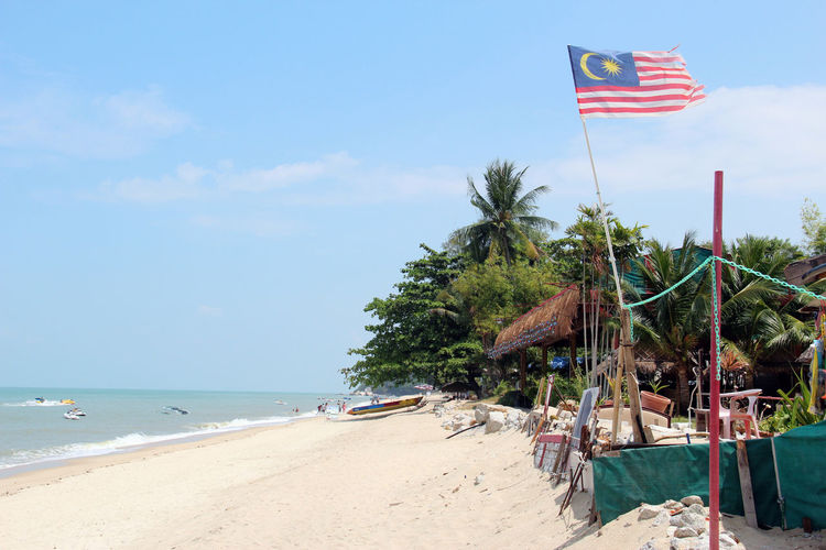 Beach in Malaysia Holiday Penang Relaxing Tree Beach Beauty In Nature Day Flag Horizon Over Water Malaysia Nature No People Outdoors Palm Tree Patriotism Sand Scenics Sea Sky Tree Water