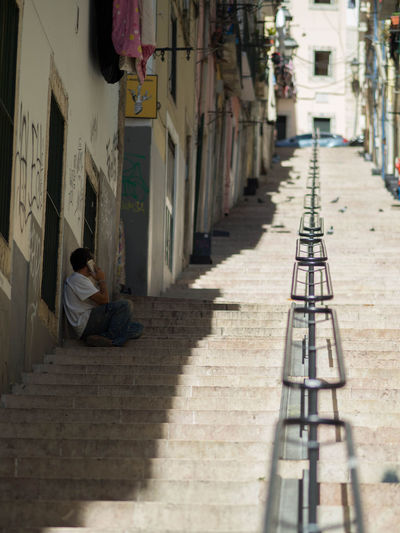 Portugal Siesta Sitting Sitting Outside Stairs Day Lisbon Narrow Street One Person Real People Sitting In The Shade Street Talking On The Phone