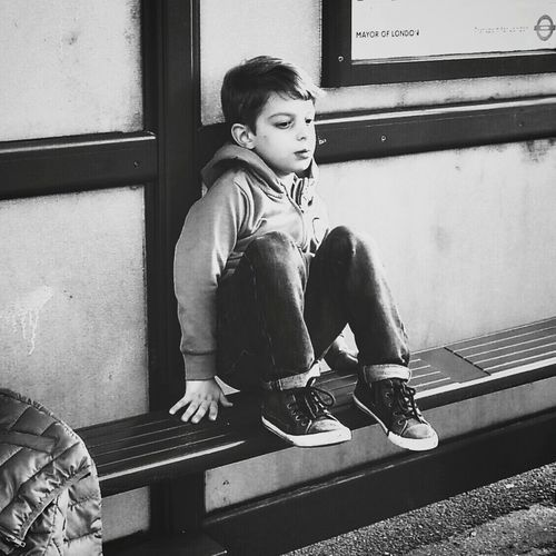 Boy Sitting At Bus Stop During Sunny Day