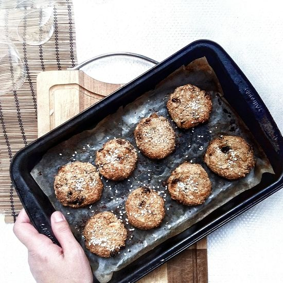 Cropped Image Of Person Holding Fresh Baked Cookies In Baking Tray On Table