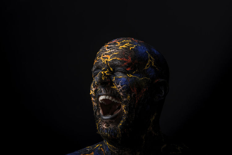 Close-Up Of Mid Adult Man With Body Paint Screaming Standing Against Black Background