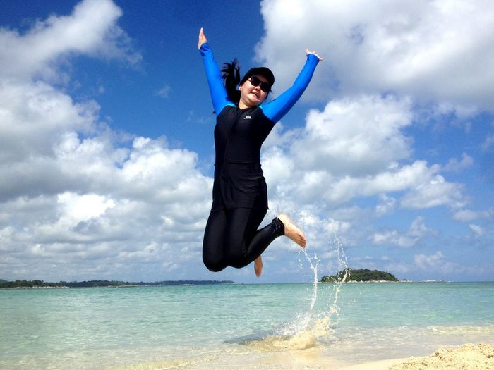 Young woman jumping in sea against sky