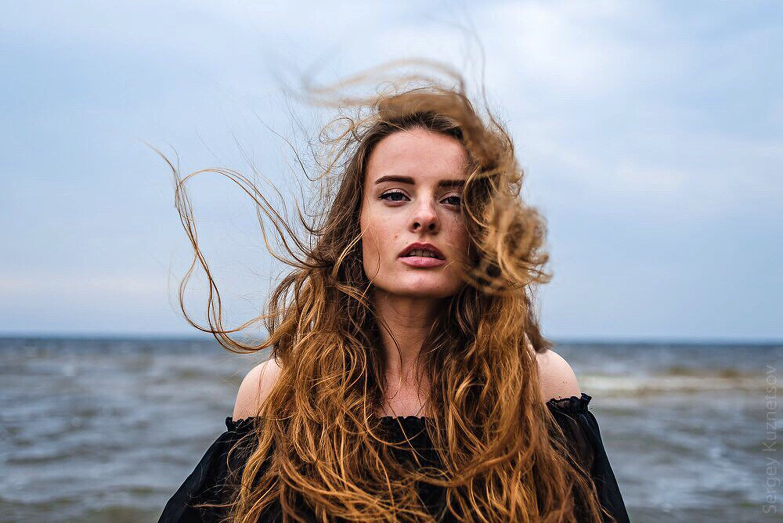 long hair, young adult, young women, looking at camera, person, portrait, lifestyles, leisure activity, brown hair, front view, headshot, sky, smiling, beach, water, focus on foreground, blond hair