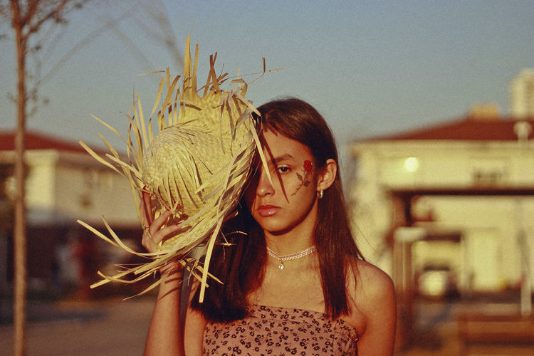 Portrait of teenage girl covering face with straw basket