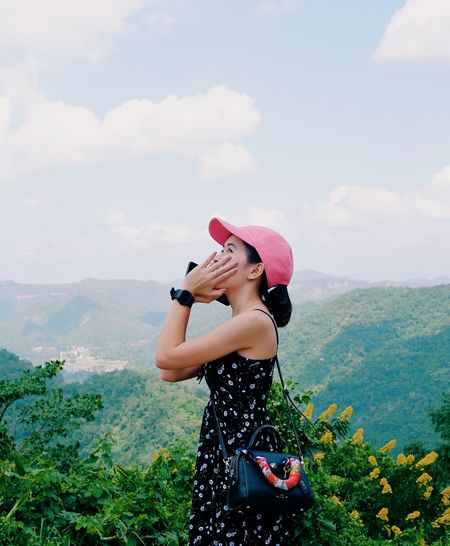 Woman wearing hat standing against mountains against sky