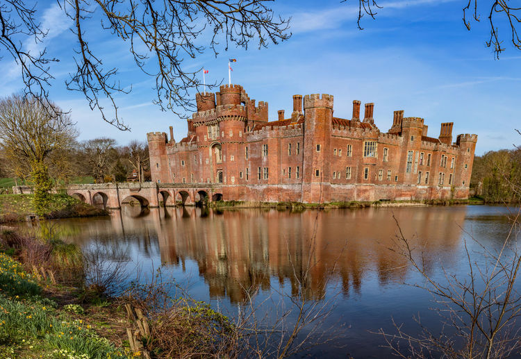 Herstmonceux Castle, Sussex, England. The oldest significant brick buildings still standing in England Castle Medieval Sun Dial Sculpture Moat William The Conqueror Travel Destinations Tourism West Sussex Phone Box Springtime Harry Potter Garden Chestnut Tree Architecture