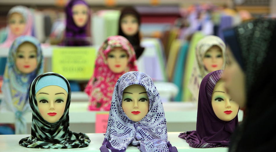 Busts wearing various patterned hijabs for sale at shop