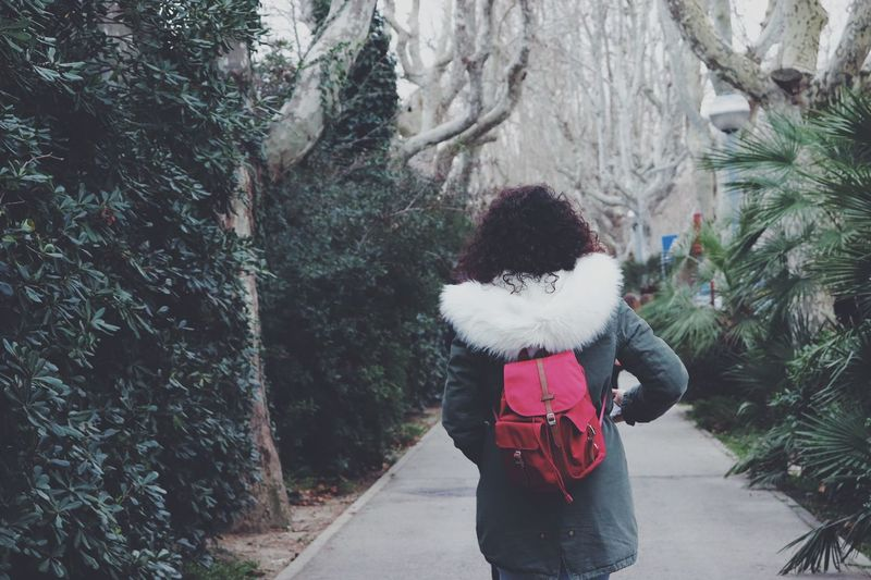 Rear view of woman with backpack standing on footpath