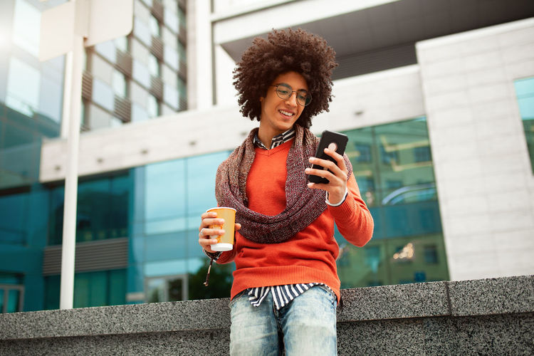 Low Angle View Of Smiling Young Man Using Mobile Phone Against Buildings In City