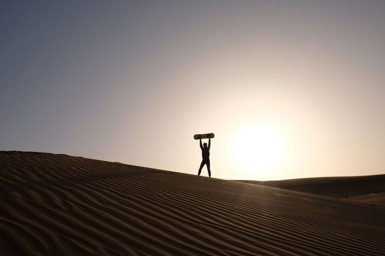 Man with skateboard standing on desert against clear sky during sunset
