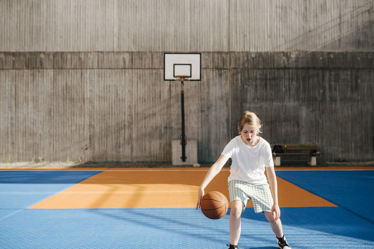 Full length of boy playing with ball on basketball court