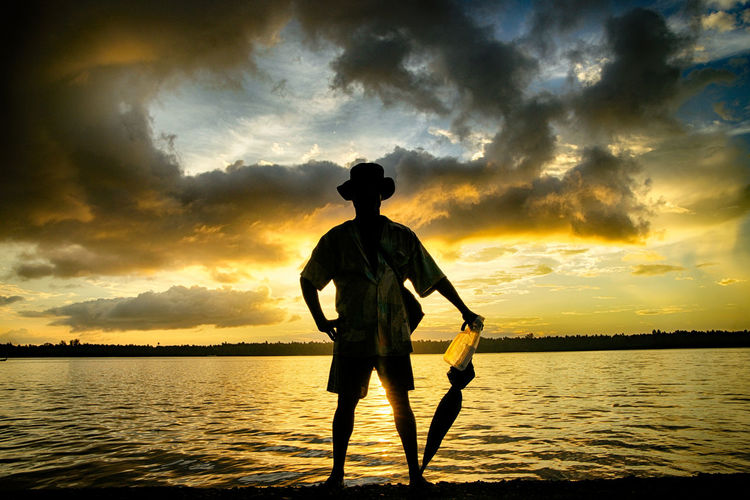 Sunset Water Sky Cloud - Sky Silhouette Beauty In Nature Scenics - Nature Standing Real People One Person Sea Men Nature Tranquility Tranquil Scene Waterfront Leisure Activity Orange Color Outdoors