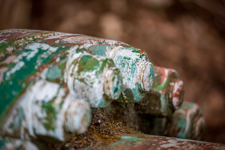 Selective shallow focus of big nuts and bolts covered in layers of rust and old paint.